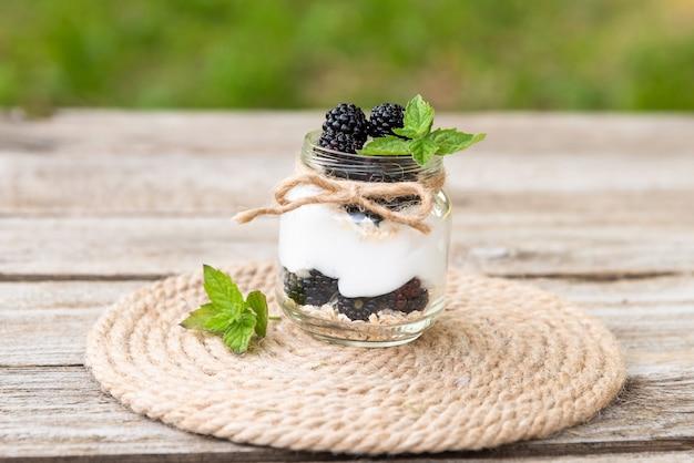 Pyszny jogurt naturalny z jeżynami i liśćmi mięty. na świeżym powietrzu. w szklanych słoikach.