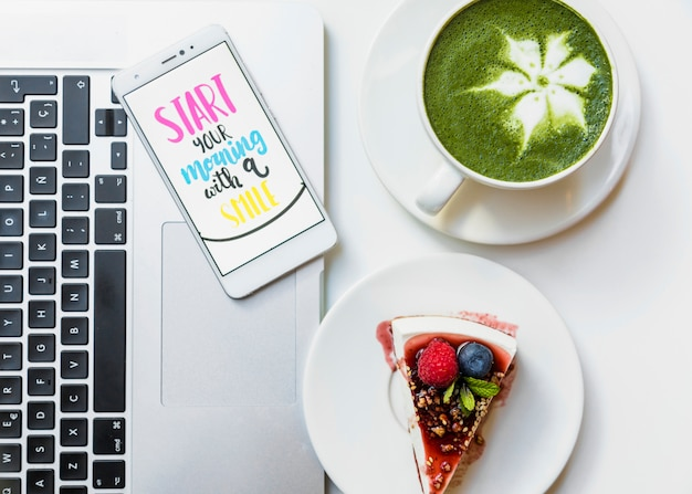 Pyszny kawałek ciasta; kubek herbaty matcha i telefon komórkowy z wiadomości na laptopie na stole