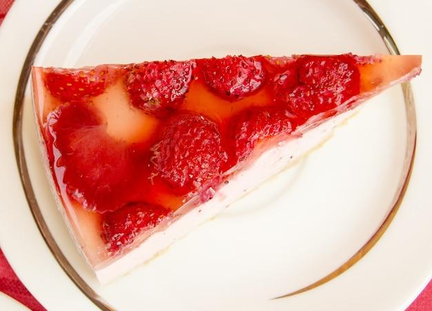 Pyszny kawałek sernika truskawkowego na białym talerzu, na stole z czerwoną serwetką w kratkę, widok z góry.