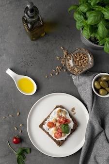 Pyszny kawałek tostu z pomidorkami koktajlowymi i oliwą z oliwek