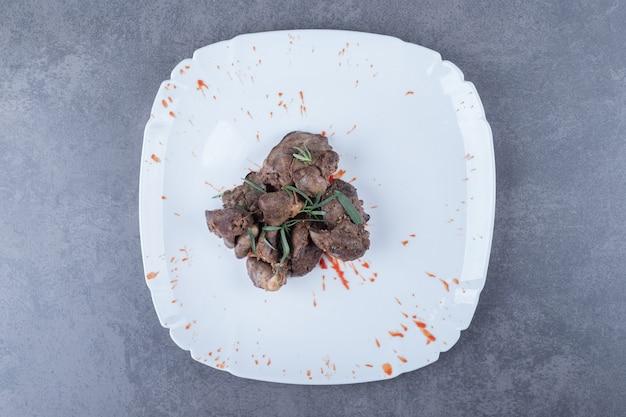 Pyszny kebab z wątroby na białym talerzu.