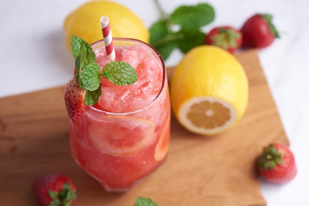 Pyszny koktajl truskawkowo-cytrynowy przyozdobiony świeżą truskawką i miętą w szkle. nieostrość. piękna przekąska różowa truskawka, dobre samopoczucie i koncepcja odchudzania.