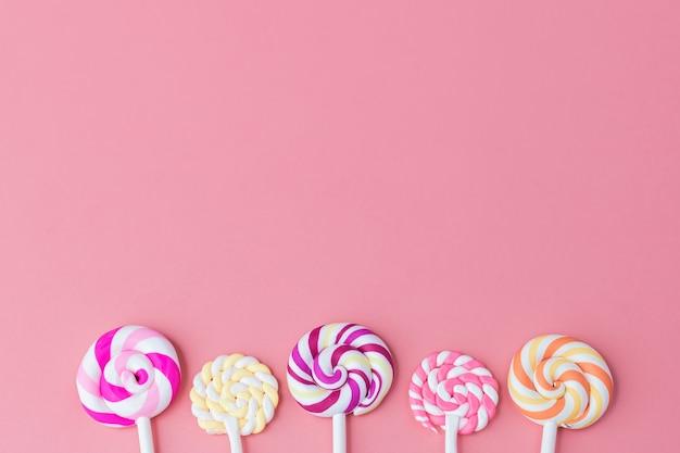 Pyszny kolorowy lizak na różowym tle z miejscem na kopię dla koncepcji przekąsek
