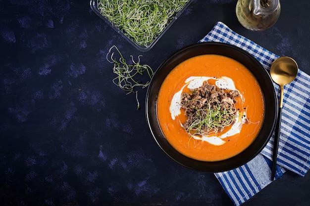 Pyszny krem z dyni z pieczonym farszem z mielonego mięsa wołowego w misce na ciemnym stole. święto dziękczynienia. widok z góry, z góry