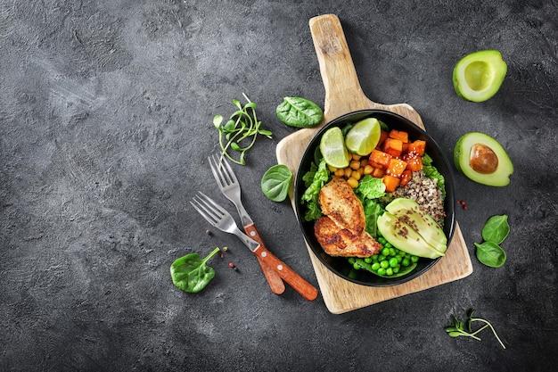 Pyszny lunch z komosą ryżową, awokado, ziemniakiem pot, smażonym kurczakiem i przyprawą na ciemnym tle. widok z góry.