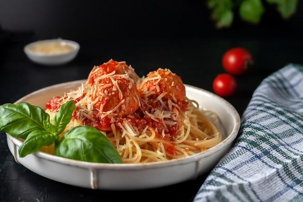 Pyszny makaron spaghetti z klopsikami, parmezanem i sosem pomidorowym na talerzu