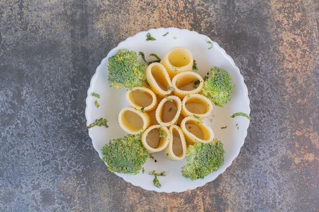 Pyszny makaron z brokułami na białym talerzu.