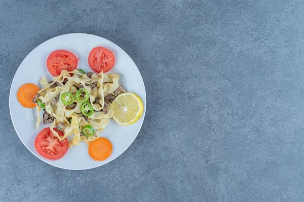 Pyszny makaron z warzywami na białym talerzu.