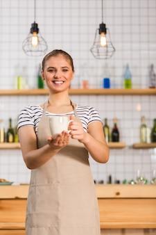 Pyszny napój. zadowolona szczęśliwa miła kobieta uśmiecha się i patrzy na ciebie trzymając kubek wypełniony pyszną kawą