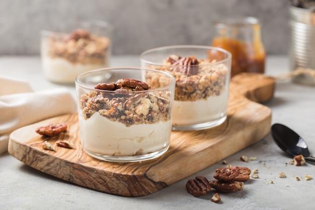 Pyszny naturalny jogurt parfait z karmelem, orzechami pekan na conctere tle