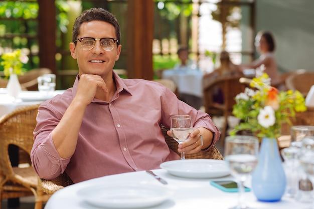 Pyszny obiad. pełen wdzięku uśmiechnięty mężczyzna ubrany w różową koszulę i czarne okulary pyszną kolację