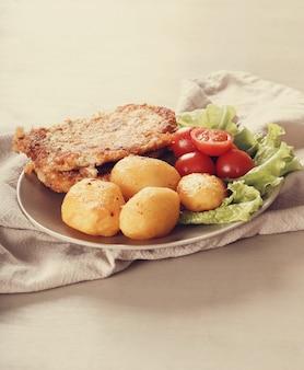 Pyszny obiad ze stekami, gotowanymi ziemniakami i sałatką