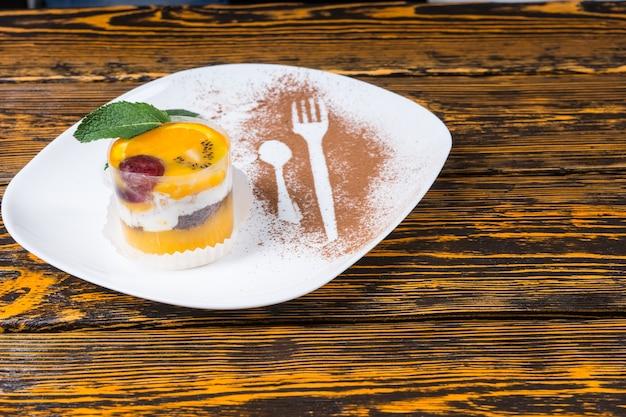 Pyszny owocowy mus cytrusowy z pomarańczą i jagodami przyozdobionymi miętą na talerzu z sylwetkami widelca i łyżki w proszku kakaowym, rustykalny drewniany stół tło z copyspace