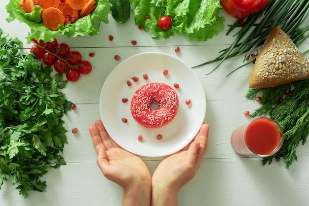Pyszny pączek leży na talerzu i je, aby go zjeść. problemy prawidłowego odżywiania i koncepcja wyboru między zdrowym a nie zdrowym jedzeniem