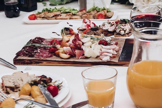 Pyszny półmisek wędlin na stole. widok na przyjęcie weselne z półmiskiem wędlin, sokiem z owoców i jagód oraz talerzami z daniem głównym.