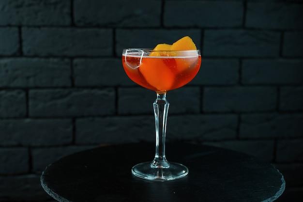 Pyszny pomarańczowo-czerwony koktajl martini z tonikiem wódki i kawałkami brzoskwiń i jabłek leży na stole w kawiarni z czarnym drewnianym stołem. designerski koktajl w kryształowym szkle vintage.
