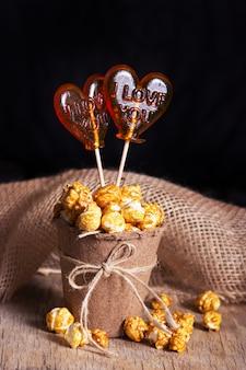 Pyszny popcorn karmelowy w papierowym kubku i lizakach