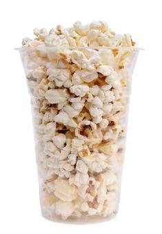 Pyszny popcorn w przezroczystym plastikowym kubku na białym tle.