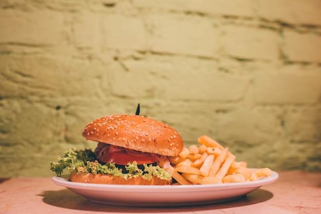 Pyszny, pyszny, tłusty burger z sałatą, pomidorem i spotkaniem w środku.