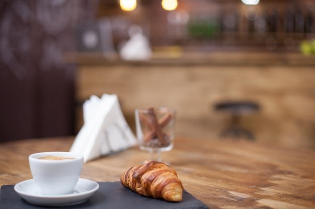 Pyszny rogalik podawany z filiżanką ciepłej kawy. vintage kawiarnia. świeżo upieczone.