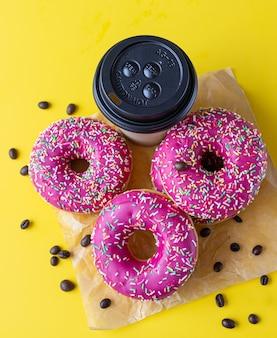 Pyszny różowy deser w glazurze z kolorową posypką, filiżanką kawy na wynos i ziarnami kawy. niezdrowe jedzenie.