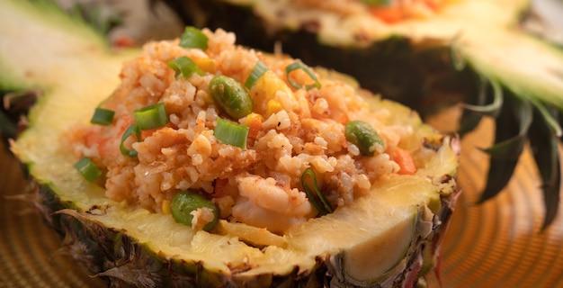 Pyszny, rzeźbiony ananas, podawany jako miska i pojemnik nadziewany świeżym ananasem, sosem pomidorowym, owocami morza i smażonym ryżem