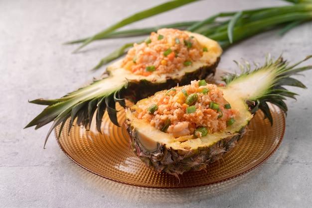 Pyszny rzeźbiony ananas służył jako miska do pojemnika na łódź nadziewana świeżym ananasem, pomidorem, sosem, smażonym ryżem z owocami morza.
