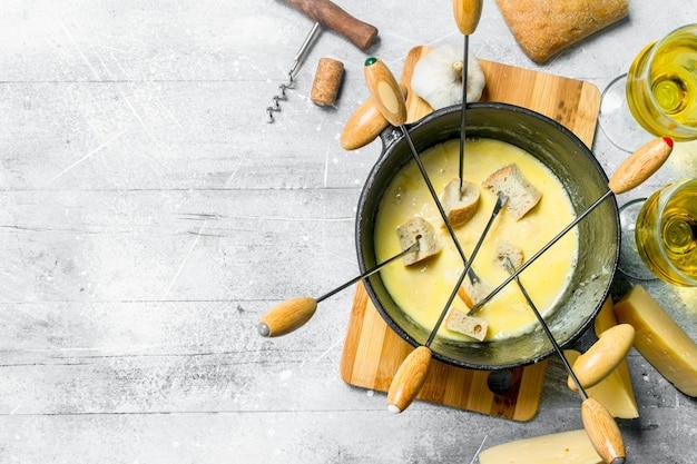 Pyszny ser fondue z pieczywem i białym winem. na tle rustykalnym