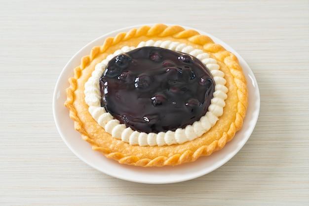 Pyszny sernik jagodowy na białym talerzu