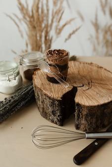 Pyszny słodki budyń czekoladowy i sztućce na drewnianej teksturze