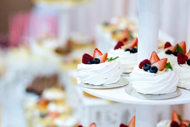 Pyszny słodki bufet z babeczkami macaron, batonik ze słodkimi babeczkami i bezami oraz inne desery