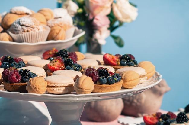 Pyszny słodki bufet z babeczkami, makaronikami, innymi deserami, niebieskim wzorem