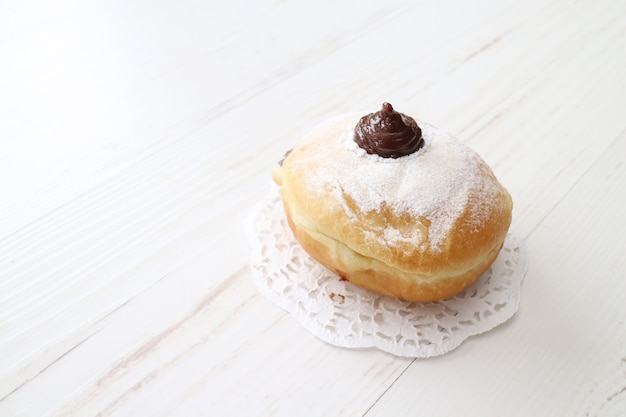 Pyszny słodki pączek z polewą czekoladową na białym stole