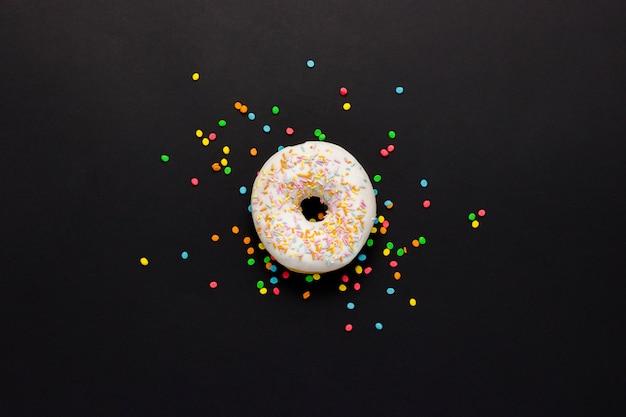 Pyszny, słodki, świeży pączek, wielokolorowe ozdobne cukierki na czarnym tle. koncepcja śniadania, fast foodu, kawiarni, piekarni. leżał płasko, widok z góry.