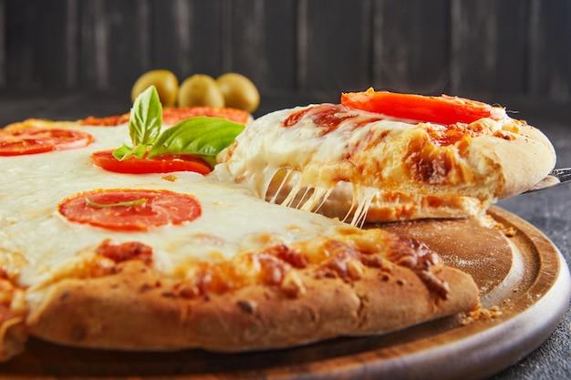 Pyszny smak pizzy i plasterków sera z mozzarellą i pomidorami. trójkątna pizza z rozciągającym się serem i przyprawami