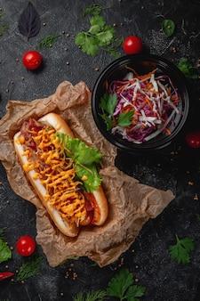 Pyszny soczysty hot dog z sosem serowym, pomidorem i świeżymi ziołami w asortymencie, kanapka w menu restauracji fast food na ciemnym kamiennym stole. zdrowa opcja fast foodów.