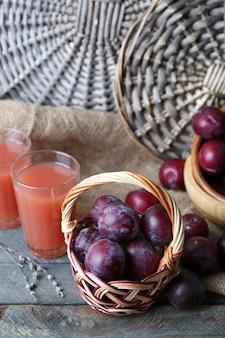 Pyszny sok śliwkowy z owocami na wiklinowej powierzchni