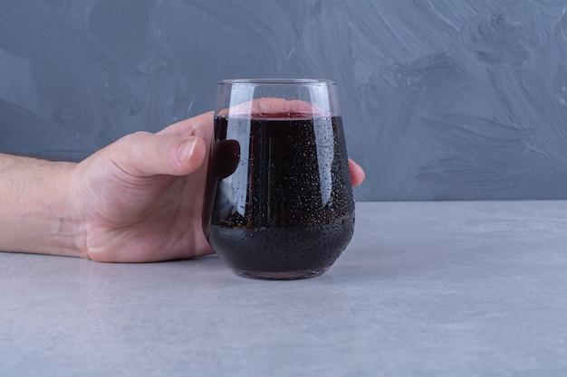 Pyszny sok z granatów w szklance na marmurowym stole.