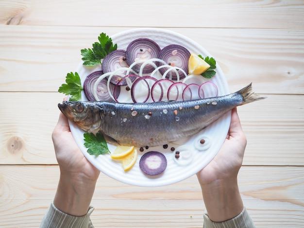 Pyszny solony śledź rybny na talerzu. kuchnia śródziemnomorska i rosyjska.