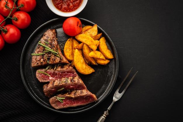 Pyszny stek wołowy z sałatką, aromatycznymi ziołami, pomidorami i ziemniakami
