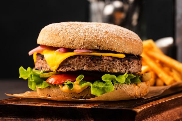 Pyszny świeży domowy cheeseburger z marynowaną cebulą i czerwoną papryką