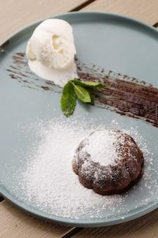 Pyszny świeży kremówka z gorącą czekoladą, lodami i miętą podany na talerzu.