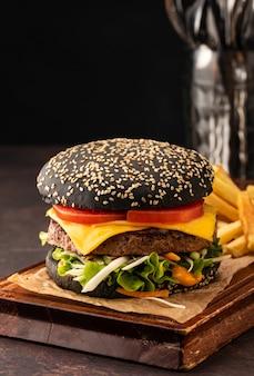 Pyszny, świeży, soczysty domowy cheeseburger w czarnej bułce z pomidorami i sałatką