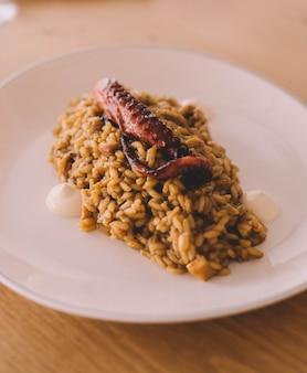 Pyszny talerz dla smakoszy ryżu z macką ośmiornicy w luksusowej morskiej restauracji europejskiej