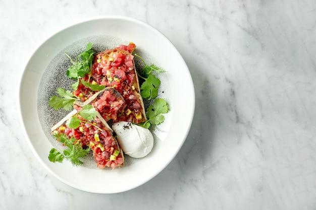 Pyszny tatar z tuńczyka z awokado, kolendrą, podawany na grzankach żytnich na białym talerzu z jajkiem w koszulce. przekąska kuchni japońskiej
