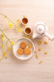 Pyszny tort księżycowy na święto środka jesieni z pięknym wzorem, ozdobiony żółtymi kwiatami i herbatą