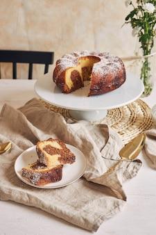 Pyszny tort w kształcie pierścienia ułożony na białym talerzu, a obok niego biały kwiatek