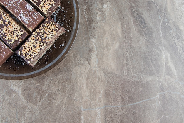 Pyszny wafel czekoladowy z orzechami na talerzu na marmurze.