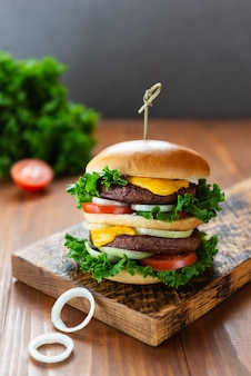 Pyszny wegański cheeseburger na drewnianej desce