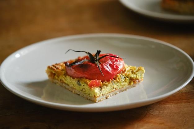 Pyszny wegetariański plasterek płaskiego chleba z pomidorem na talerzu